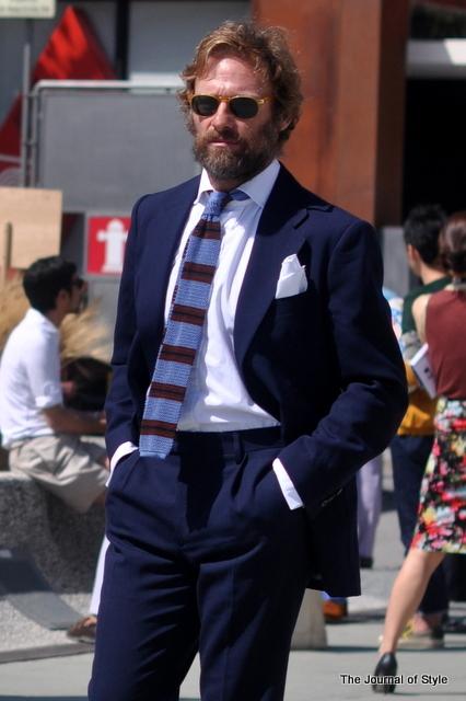 En klassisk marineblå habit med casual strikket slips og stor lommeklud i brystlommen.